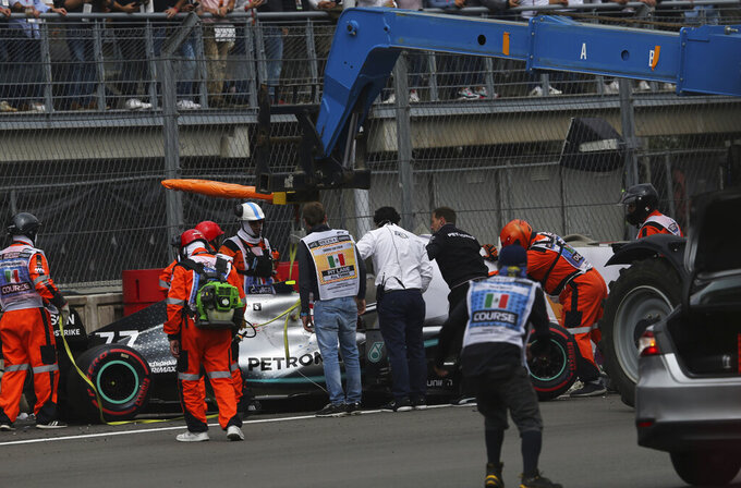 Mercedes driver Valtteri Bottas' car is lifted with a crane after he crashed in a curve during the qualifying session for the Formula One Mexico Grand Prix auto race at the Hermanos Rodriguez racetrack in Mexico City, Saturday, Oct. 26, 2019. (AP Photo/Marco Ugarte)
