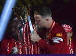 Liverpool's Jordan Henderson kisses the English Premier League trophy after it was presented following the Premier League soccer match between Liverpool and Chelsea at Anfield stadium in Liverpool, England, Wednesday, July 22, 2020. (Paul Ellis, Pool via AP)