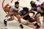Houston guard Cameron Tyson, left, grabs a loose ball from Tulsa guards Brandon Rachal, center, and Elijah Joiner, right, during the first half of an NCAA college basketball game Wednesday, Jan. 20, 2021, in Houston. (AP Photo/Eric Christian Smith)