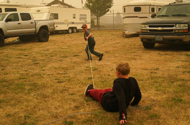 FILE - In this Sept. 13, 2020, file photo, Bransen Faulhaber, 7, lassoes Kole Michael Jones at an evacuation center for the Riverside Fire at the Clackamas County Fairgrounds in Canby, Ore. When wildfires raged across the state earlier this month authorities initially said 500,000 people had fled their homes, but later said that figure was the number of people under some level of evacuation notice. The actual number of people who fled their homes was much smaller. (AP Photo/John Locher)
