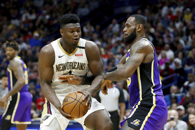 Los Angeles Lakers forward LeBron James (23) reaches for the ball as New Orleans Pelicans forward Zion Williamson (1) drives to the basket in the second half of an NBA basketball game in New Orleans, Sunday, March 1, 2020. (AP Photo/Rusty Costanza)