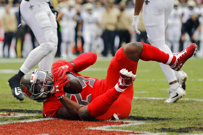 Tampa Bay Buccaneers running back Peyton Barber (25) scores on a 6-yard touchdown pass against the New Orleans Saints during the first half of an NFL football game Sunday, Nov. 17, 2019, in Tampa, Fla. (AP Photo/Mark LoMoglio)