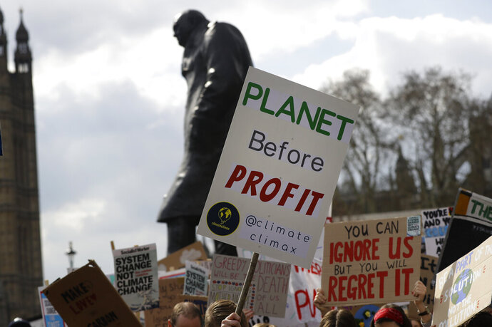 FILE - In this Friday, April 12, 2019 file photo, climate change demonstrators hold banners in front of the Winston Churchill Statue during a protest near Parliament in London. An independent committee that advises the British government on climate change says the UK should target net-zero emissions of greenhouse gases by 2050, recommending the rapid adoption of policies to change everything from how people heat their homes to what they eat. The report released Thursday, May 2 by the Committee on Climate Change stresses that it is time for ambitious goals to curb the emissions that cause climate change. (AP Photo/Kirsty Wigglesworth, file)
