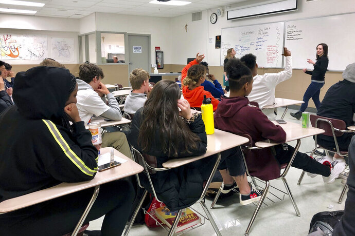 FILE - In this April 15, 2019, file photo, instructors from Raphael House lead a classroom discussion about consent and healthy relationships with a class of sophomores at Central Catholic High School in Portland, Ore. Most young Americans believe in the value of higher education, but many also believe that a high school diploma alone is enough for success, and they view job training as better preparation than any type of college degree, according to a poll by The Associated Press-NORC Center for Public Affairs Research. (AP Photo/Gillian Flaccus, File)