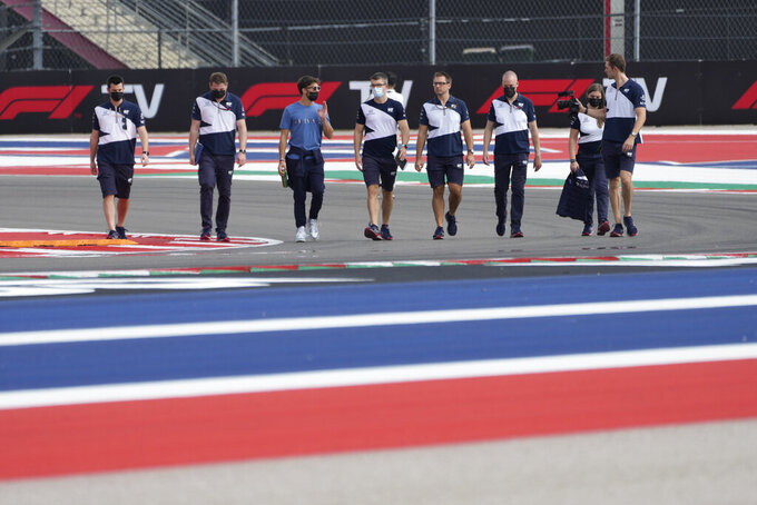 AlphaTauri driver Pierre Gasly, third from left, of France, walks the course with his crew before the Formula One U.S. Grand Prix auto race at the Circuit of the Americas, Thursday, Oct. 21, 2021, in Austin, Texas. (AP Photo/Nick Didlick)