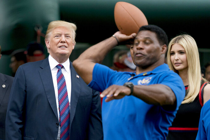 FILE - In this May 29, 2018 file photo, President Donald Trump, left, and his daughter Ivanka Trump, right, watch as former football player Herschel Walker, center, throws football's during White House Sports and Fitness Day on the South Lawn of the White House in Washington. The U.S. Senate nomination in a premier battleground like Georgia should be a plum political prize, but a year before Republican voters choose a nominee for the 2022 midterms, they have no clear options. The wildcard is whether football hero Herschel Walker runs and brings the endorsement of former President Donald Trump. (AP Photo/Andrew Harnik)