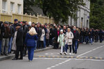 People stand in line to a polling station during parliamentary elections in Moscow, Russia, Friday, Sept. 17, 2021. Russia has begun three days of voting for a new parliament that is unlikely to change the country's political complexion. There's no expectation that United Russia, the party devoted to President Vladimir Putin, will lose its dominance in the State Duma. (AP Photo/Pavel Golovkin)
