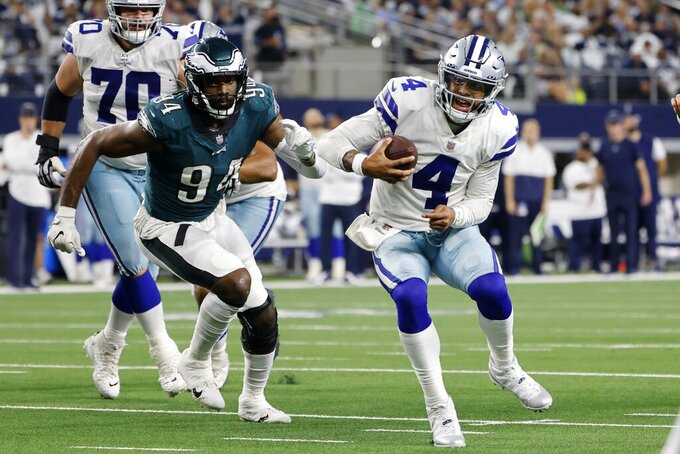 Philadelphia Eagles defensive end Josh Sweat (94) chases Dallas Cowboys quarterback Dak Prescott (4) out of the pocket in the second half of an NFL football game in Arlington, Texas, Monday, Sept. 27, 2021. (AP Photo/Michael Ainsworth)