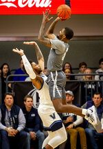 Xavier forward Naji Marshall (13) shoots over Villanova guard Justin Moore (5) during the first half of an NCAA college basketball game, Monday, Dec. 30, 2019, in Villanova, Pa. (AP Photo/Laurence Kesterson)