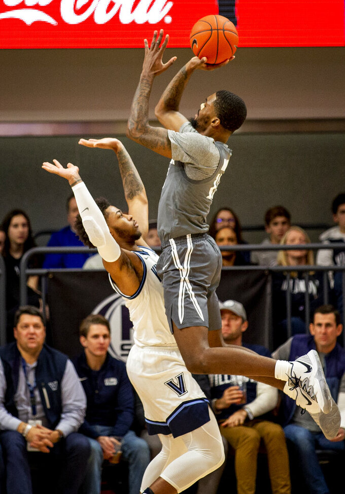 Xavier forward Naji Marshall (13) shoots over Villanova guard Justin Moore (5) during the first half of an NCAA college basketball game, Monday, Dec. 30, 2019, in Villanova, Pa. (AP Photo/Laurence Kesterson)