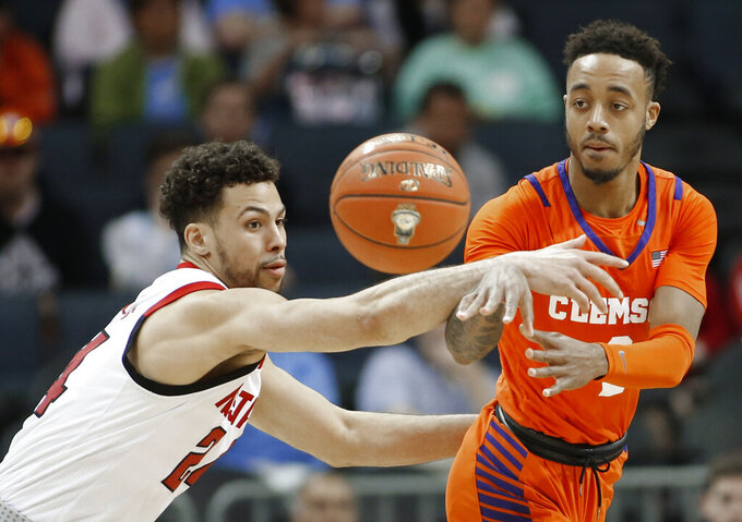 Clemson's Marcquise Reed (2) passes the ball past North Carolina State's Devon Daniels (24) during the first half of an NCAA college basketball game in the Atlantic Coast Conference tournament in Charlotte, N.C., Wednesday, March 13, 2019. (AP Photo/Nell Redmond)