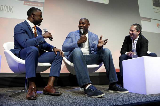 Former Philadelphia Eagles NFL football running back Brian Westbrook, left, talks with former Philadelphia Phillies baseball first baseman Ryan Howard, center, and Wayne Kimmel, partner at SeventySix Capital, during a panel talking about the move from professional athlete to entrepreneur at the Betting On Sports America conference, Wednesday, April 24, 2019, in Secaucus, N.J. (AP Photo/Julio Cortez)