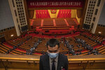 A security official wearing a protective face mask stands guard as delegates leave after the second plenary session of China's National People's Congress (NPC) at the Great Hall of the People in Beijing, Monday, May 25, 2020. (Roman Pilipey/Pool Photo via AP)