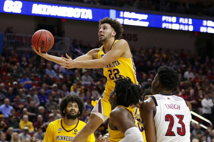 Minnesota's Gabe Kalscheur (22) goes for a layup as Louisville's Steven Enoch (23) watches, during the second half of a first round men's college basketball game in the NCAA Tournament in Des Moines, Iowa, Thursday, March 21, 2019. (AP Photo/Nati Harnik)