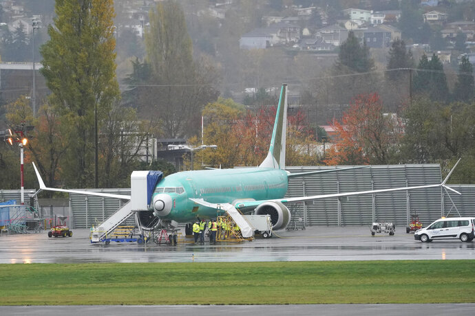 FILE - In this Wednesday, Nov. 18, 2020 file photo, workers stand near a Boeing 737 Max airplane parked at Renton Municipal Airport next to the Boeing assembly facility in Renton, Wash., where 737 Max airplanes are made. On Tuesday, Jan. 12, 2021, the company reported final 2020 numbers for airplane orders and deliveries, and they are down from 2019 even though the 737 Max is flying again. (AP Photo/Ted S. Warren)