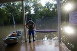 FILE- In this Aug. 16, 2016 file photo, David Key looks at the back yard of his flooded home in Prairieville, La. Memories of an epic flood that caused billions of dollars in damage had Louisiana's capital on edge Friday, July 12, 2019, as Barry gained strength in the Gulf of Mexico. (AP Photo/Max Becherer, File)