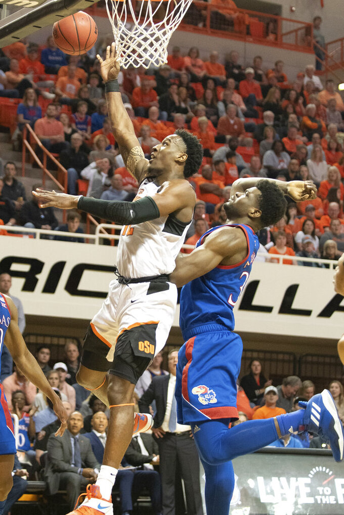 Oklahoma State forward Cameron McGriff, left, banks a shot under pressure from Kansas center Udoka Azubuike during the first half of an NCAA college basketball game in Stillwater, Okla., Monday, Jan. 27, 2020. (AP Photo/Brody Schmidt)