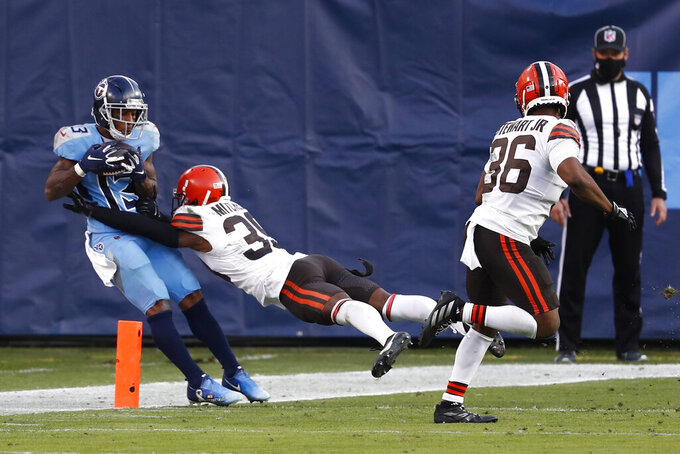 Tennessee Titans wide receiver Cameron Batson (13) catches a touchdown pass as he is hit by Cleveland Browns cornerback Terrance Mitchell (39) in the second half of an NFL football game Sunday, Dec. 6, 2020, in Nashville, Tenn. (AP Photo/Wade Payne)
