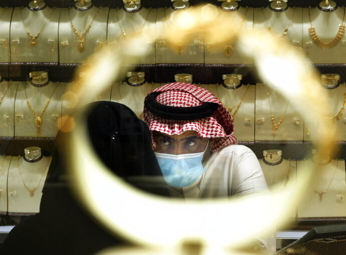 A Saudi vendor is seen through a bracelet as a woman buys jewels at the gold market a day before the expected increase of VAT from 5% to 15%, in Jiddah, Saudi Arabia, Tuesday, June 30, 2020. (AP Photo/Amr Nabil)