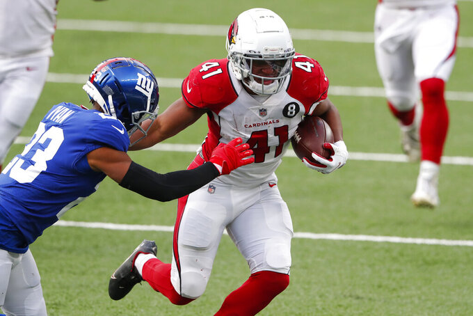 Arizona Cardinals' Kenyan Drake, right, runs the ball while trying to keep New York Giants' Logan Ryan away during the second half of an NFL football game, Sunday, Dec. 13, 2020, in East Rutherford, N.J. (AP Photo/Noah K. Murray)