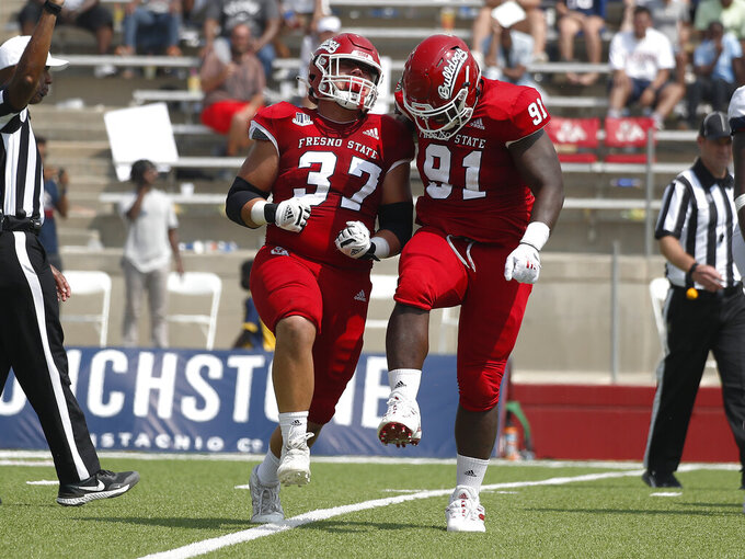 Fresno State's Ryan Boehm and Matt Lawson celebrate a sack against Connecticut during the second half of an NCAA college football game in Fresno, Calif., Saturday, Aug. 28, 2021. (AP Photo/Gary Kazanjian)