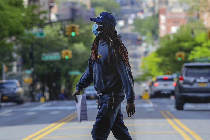 A man wearing a protective mask during the coronavirus pandemic crosses Amsterdam Avenue Wednesday, May 20, 2020, in New York. (AP Photo/Frank Franklin II)