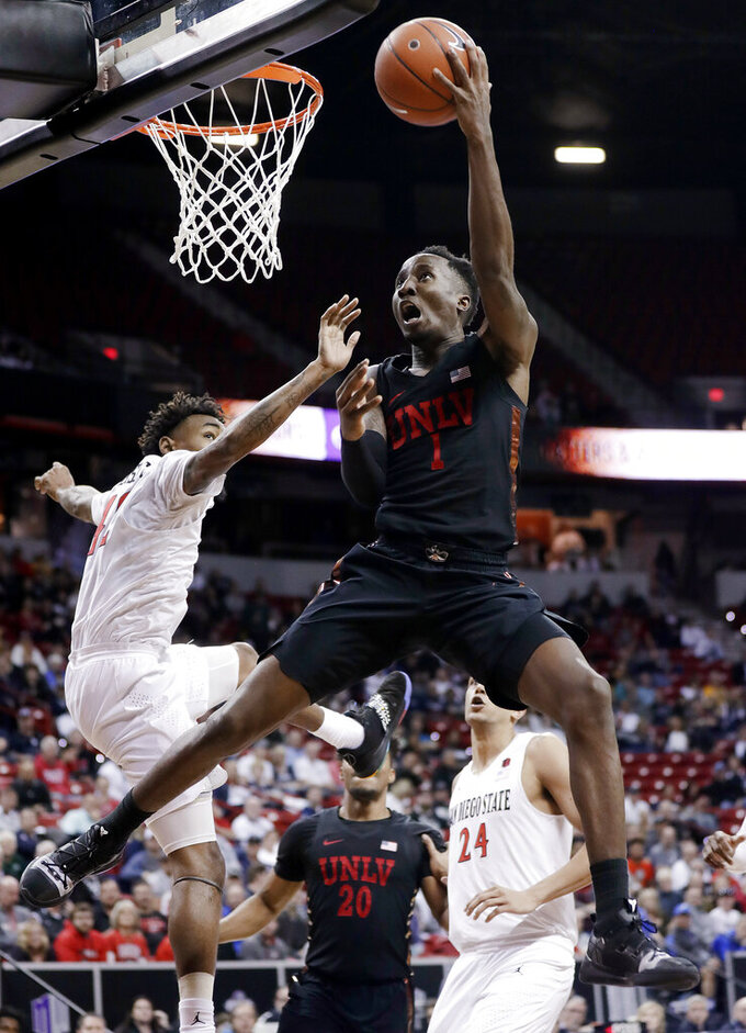 San Diego State's Jeremy Hemsley defends as UNLV's Kris Clyburn (1) shoots during the second half of an NCAA college basketball game in the Mountain West Conference men's tournament Thursday, March 14, 2019, in Las Vegas. (AP Photo/Isaac Brekken)