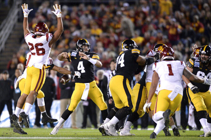 Southern California safety Talanoa Hufanga (15) knocks the ball out of the hands of Iowa quarterback Nate Stanley (4) who was attempting to throw a pass during the first half of the Holiday Bowl NCAA college football game Friday, Dec. 27, 2019, in San Diego. (AP Photo/Orlando Ramirez)
