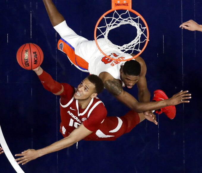 Arkansas forward Daniel Gafford (10) reaches for a rebound in front of Florida center Kevarrius Hayes (13) in the second half of an NCAA college basketball game at the Southeastern Conference tournament Thursday, March 14, 2019, in Nashville, Tenn. Florida won 66-50. (AP Photo/Mark Humphrey)