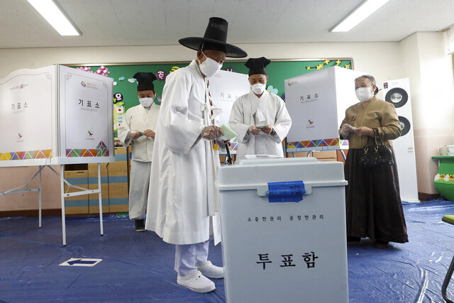 A South Korean Confucian scholar wearing a face mask to help protect against the spread of the new coronavirus casts his vote for the parliamentary elections at a polling station in Nonsan, South Korea, Wednesday, April 15, 2020. South Korean voters wore masks and moved slowly between lines of tape at polling stations on Wednesday to elect lawmakers in the shadows of the spreading coronavirus. (Kim Jun-beom/Yonhap via AP)
