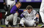 Colorado Rockies trainer Heath Townsend, left, helps Brendan Rodgers after he was hit by a pitch in the helmet by Washington Nationals starting pitcher Josiah Gray in the first inning of a baseball game Monday, Sept. 27, 2021, in Denver. (AP Photo/David Zalubowski)