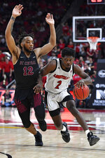 Louisville guard Darius Perry (2) drives around the defense of North Carolina Central guard Jordan Perkins (12) during the second half of an NCAA college basketball game in Louisville, Ky., Sunday, Nov. 17, 2019. (AP Photo/Timothy D. Easley)