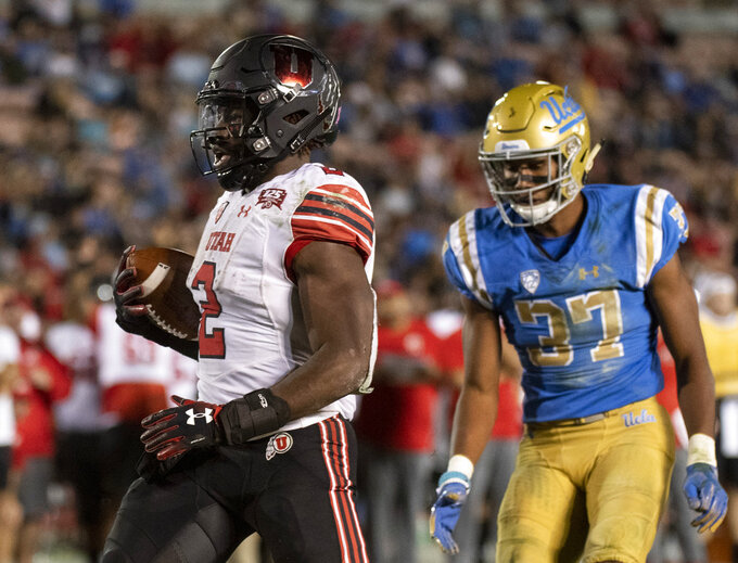 Utah running back Zack Moss, left, scores touchdown past UCLA defensive back Quentin Lake during the second half of an NCAA college football game Friday, Oct. 26, 2018, in Pasadena, Calif. (AP Photo/Kyusung Gong)