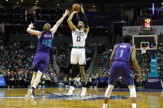 Boston Celtics' Jayson Tatum (0) aims a three-pointer as Charlotte Hornets' Cody Zeller (40) stretches to defend during the first half of an NBA basketball game in Charlotte, N.C., Tuesday, Dec. 31, 2019. (AP Photo/Bob Leverone)