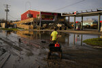 A man goes for gas at a hurricane-damaged gas station in the aftermath of Ida, Monday, Sept. 6, 2021, in Grand Isle, La. (AP Photo/John Locher)
