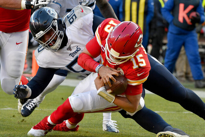 Kansas City Chiefs' Patrick Mahomes (15) runs for a touchdown against Tennessee Titans defensive tackle DaQuan Jones (90) during the first half of the NFL AFC Championship football game Sunday, Jan. 19, 2020, in Kansas City, MO. (AP Photo/Ed Zurga)