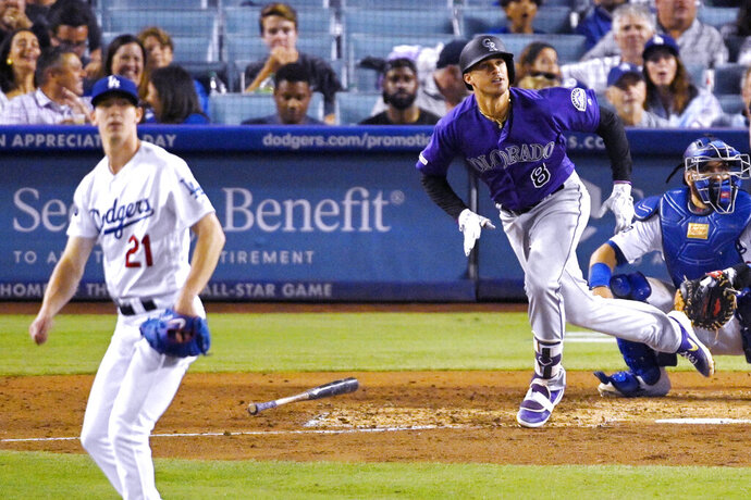 Colorado Rockies' Josh Fuentes, center, runs to first as he hits a solo home run while Los Angeles Dodgers starting pitcher Walker Buehler, left, and catcher Russell Martin watch during the seventh inning of a baseball game Saturday, Sept. 21, 2019, in Los Angeles. (AP Photo/Mark J. Terrill)