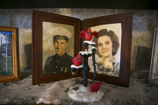This Feb. 17, 2020 photo shows an old photograph of Eddie Vincek and his wife, Mary Vincek,  on a shelf in their home in Chesapeake, Va..  Seventy-five years ago, Vincek beat some other odds — surviving the Battle of Iwo Jima, one of the last and bloodiest struggles of World War II in the Pacific.  (Kristen Zeis/The Virginian-Pilot via AP)