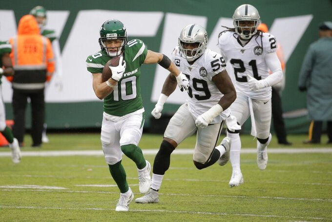 New York Jets wide receiver Braxton Berrios (10) runs away from Oakland Raiders' Tahir Whitehead (59) and D.J. Swearinger (21) during the second half of an NFL football game Sunday, Nov. 24, 2019, in East Rutherford, N.J. The Jets won 34-3. (AP Photo/Seth Wenig)
