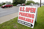 A sign for parking is displayed in front of a private lot as vehicles drive slowly in traffic along County Road 39 near the site of the U.S. Open Golf Championship, Wednesday, June 13, 2018, in Southampton, N.Y. (AP Photo/Julio Cortez)