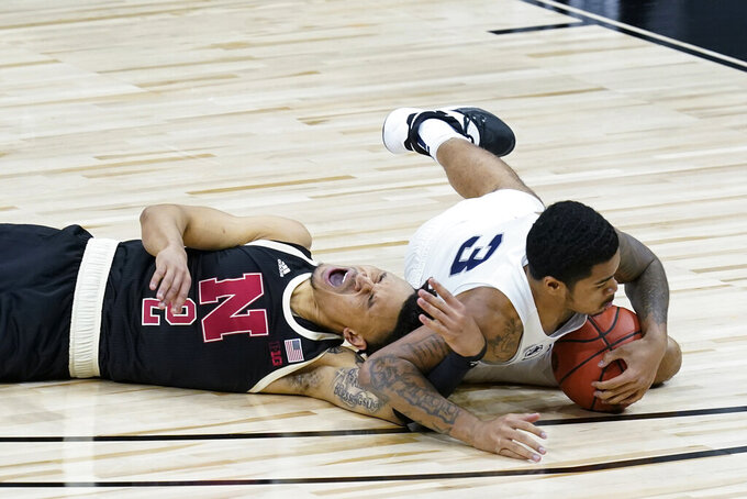 Nebraska's Trey McGowens (2) and Penn State's Sam Sessoms (3) dive for a loose ball during the second half of an NCAA college basketball game at the Big Ten men's tournament Wednesday, March 10, 2021, in Indianapolis. (AP Photo/Darron Cummings)