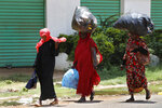 Sudanese women carry on their heads big bags of empty plastic bottles, as they walk on the street, in Khartoum, Sudan, Saturday, June 15, 2019. The top U.S. diplomat to Africa says there needs to be an