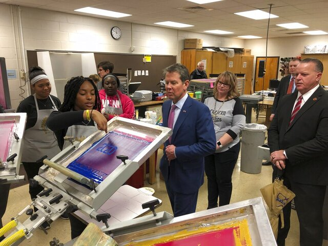 Georgia Gov. Brian Kemp looks on as McEarchern High School senior Stephany Ahanonu demonstrates screen printing in a graphic arts classroom Thursday, Feb. 13, 2020, at the high school in Powder Springs, Ga. Kemp visited the school to call on teachers and other to support his proposal for an additional $2,000 teacher pay raise in the state budget year beginning July 1, 2020. (AP Photo/Jeff Amy)