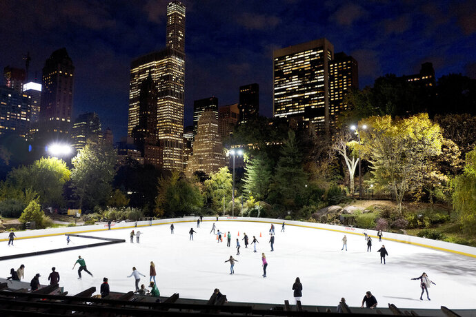 In this Thursday, Nov. 3 photo, skaters take to the ice at Wollman Rink in New York's Central Park. Skaters may notice something missing from the park's two ice rinks this winter — President Donald Trump's name, a spokeswoman for the city Parks Department, said in a statement Wednesday, Oct. 23, 2019. The Trump Organization still operates the rinks but has removed the Trump name from the outer boards, the skate rental counters and elsewhere. (AP Photo/Mark Lennihan)
