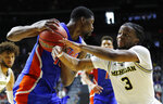 Michigan guard Zavier Simpson (3) tries to steal the ball from Florida center Kevarrius Hayes, left, during a second round men's college basketball game in the NCAA Tournament, Saturday, March 23, 2019, in Des Moines, Iowa. (AP Photo/Charlie Neibergall)