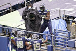 Seattle Seahawks wide receiver DK Metcalf (14) briefly takes over a broadcast camera to point at his teammates after climbing into the stands after he scored a touchdown against the New York Jets during the first half of an NFL football game, Sunday, Dec. 13, 2020, in Seattle. (AP Photo/Ted S. Warren)