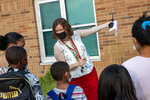 Jefferson Elementary School Principal LeeAnn Stephan directs students as they return to school in Holland, Mich., on Wednesday, Aug. 26, 2020. (Cory Morse/The Grand Rapids Press via AP)
