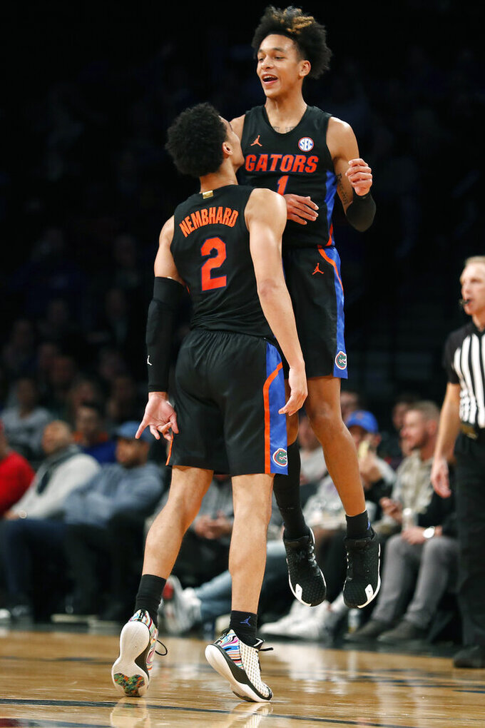Florida guard Tre Mann (1) reacts with teammate Andrew Nembhard (2) after scoring in the second half of an NCAA college basketball game against Providence at Barclays Center, Tuesday, Dec. 17, 2019, in New York. (AP Photo/Michael Owens)
