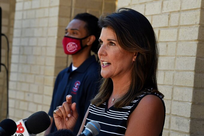 Former South Carolina Gov. Nikki Haley, right, speaks with reporters after a tour of the campus of South Carolina State University on Monday, April 12, 2021, in Orangeburg, S.C. Haley, often mentioned as a possible 2024 GOP presidential contender, said Monday that she would not seek her party's nomination if former President Donald Trump opts to run a second time. (AP Photo/Meg Kinnard)