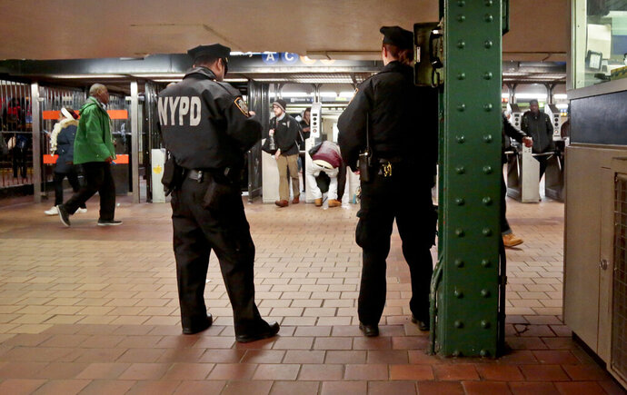 FILE - In this March 3, 2016, file photo, New York City police officers observe commuters using turnstiles at a Harlem subway station in New York. New York City's policing of subway fare beaters is drawing scrutiny from the state's attorney general for possible racial bias. (AP Photo/Bebeto Matthews, File)
